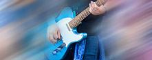 Guitarist man playing music on black electric guitar
